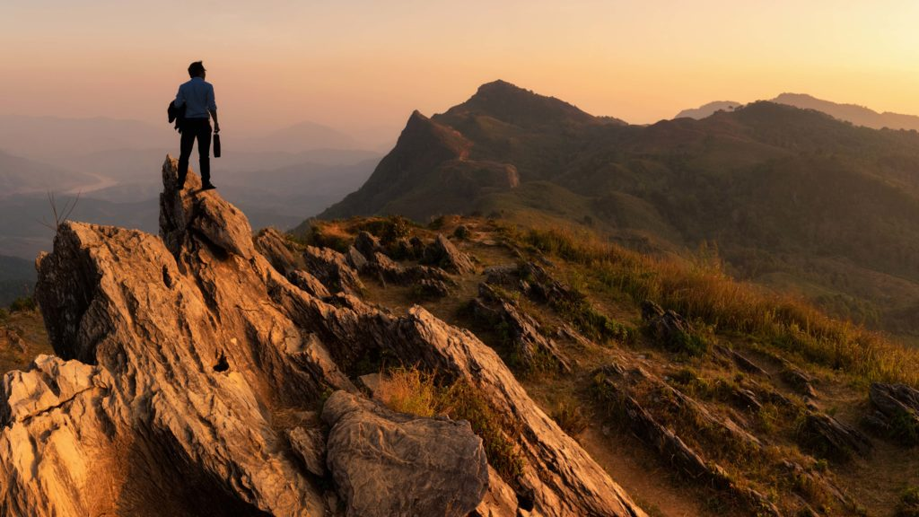 Concept vision, Young businessman wearing comfortable casual suit jacket standing holding a work bag on top of peak mountain and looking forwards, success, competition and leader concept.